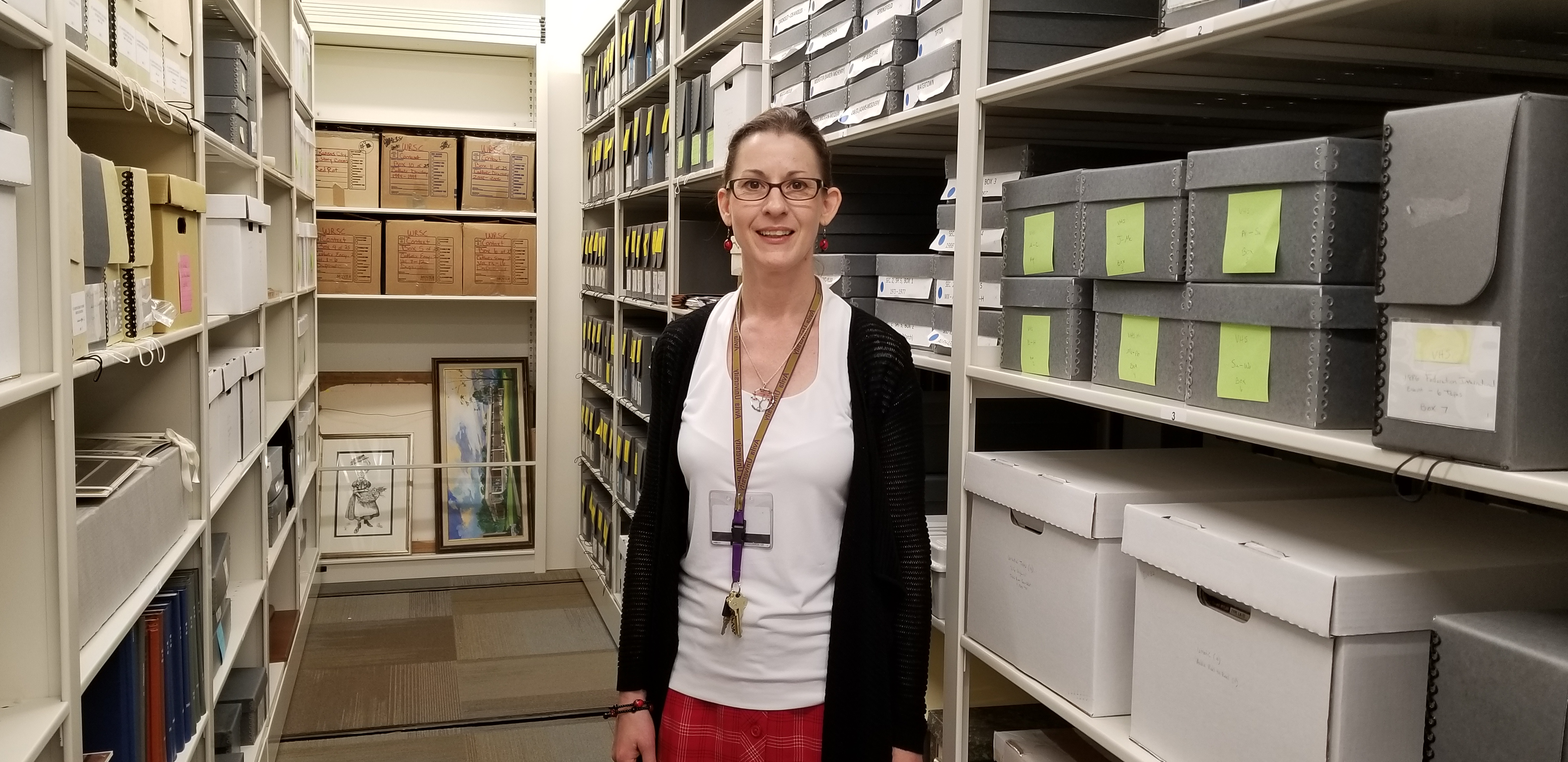 Avila Archivist Adonna Thompson standing among our collection