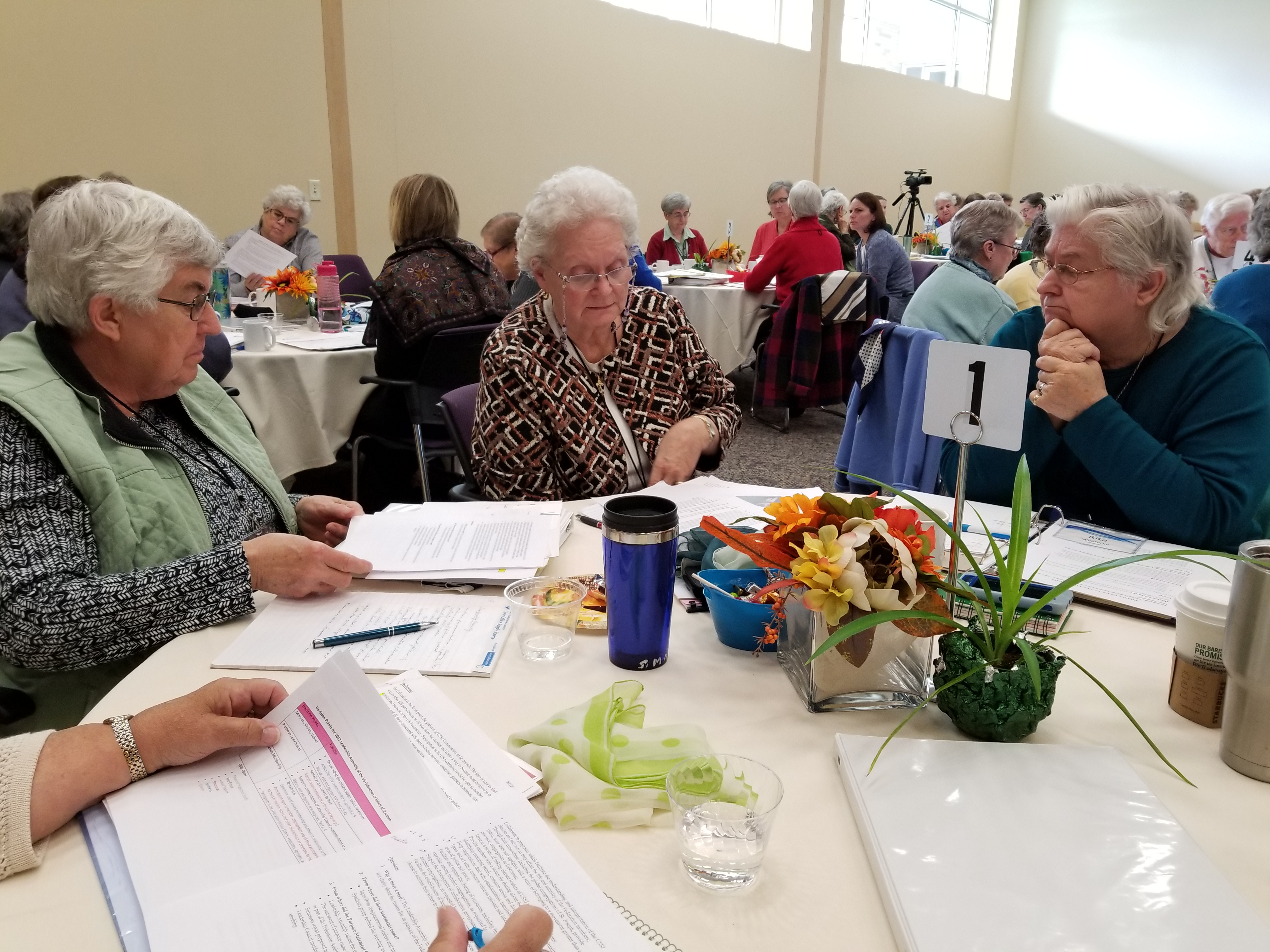 Associate director Sr. Rita Woehlcke left speaks with Srs. Mary Ann Mayer and Mary Anne Heenan at the Leadership Assembly