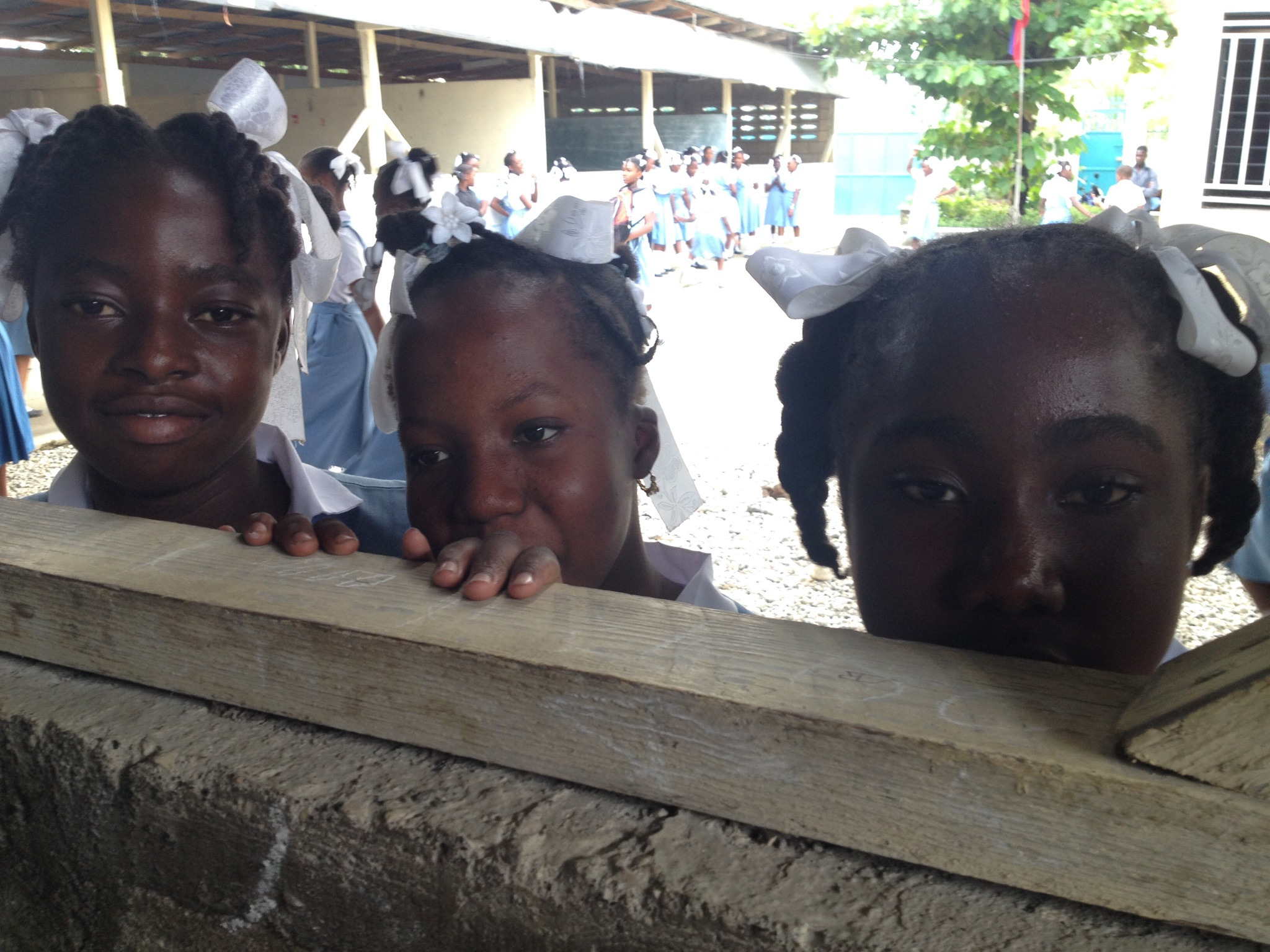 Students during recess peeking over classroom wall