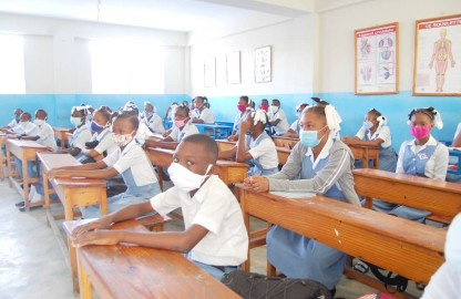 A photo of a blue and white classroom with long wooden tables spanning the room. The room is filled with male and female students wearing cloth masks and blue and white school uniforms.