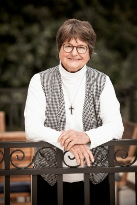 A photo of Sr. Helen Prejean from her torso and up. Sr. Helen is a white woman with short brown-gray hair, a white turtleneck, a black and white checkered vest and a silver cross on a silver chain. She is leaning on a metal fence with trees in the background