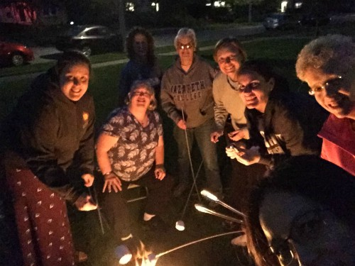The U.S. Federation novices and staff smiling around a bit of fire at night as they roast marshmallows