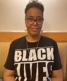 A headshot of Sr. Melinda Pellerin, an African American woman, with short curly black hair and wearing black cat-eyed glasses. She is wearing a short sleeve black t-shirt with the words Black Lives Matter on it.