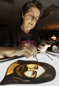 A photo of Sr. Diane Couture – a white woman with short gray hair, wire glasses and wearing a black t-shirt and marron apron – holding a point brush over her stain glass of a brown haired, bearded Jesus