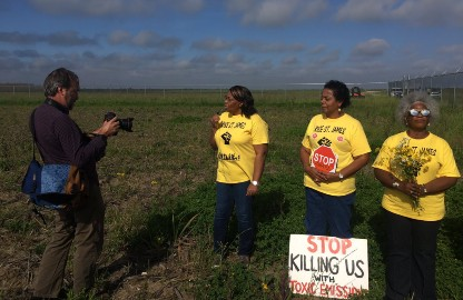 "A photo of a photographer taking a picture of three women in a field earing bright yellow rise St. James t-shirts. In front of them is a sign that says ""stop killing with toxic emissions"""