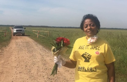 Sharon Lavigne, a black woman wearing a yellow shirt and holding a bouquet of flowers, stands on a dirt road in a field