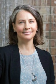 A headshot of Krisanne Vaillancourt Murphy in front of a brick wall wearing a blazer, blue geometric shirt, and a long necklace